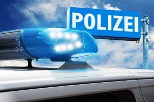 Polizeifahrzeug vor Polizeischild