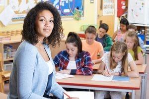 Lehrerin in der Klasse vor arbeitenden Schülern