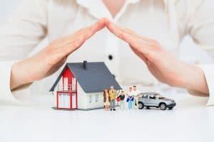 Schützende Hände über der Familie mit Haus und Auto