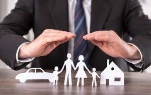 Schützende Hände über einer Familie mit Auto und Haus