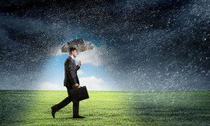 Mann mit schützendem Schirm im Regen